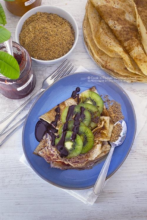 Pour le goûter, 2 crêpes vegan à la confiture, coulis de chocolat noir, sucre de canne complet et quelques tranches de kiwis pour la fraîcheur.